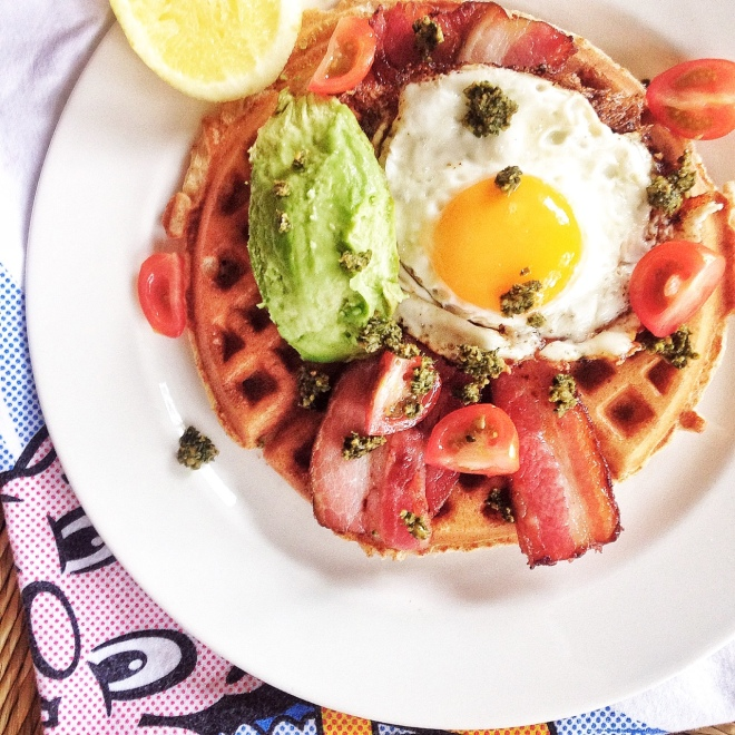 Plain waffle with egg, bacon, avocado, kale and sunflower seed pesto and tomatoes.